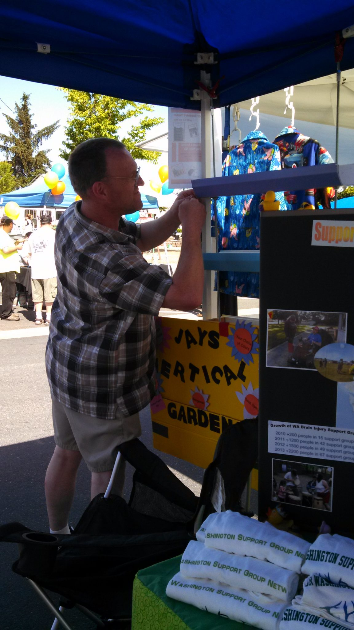"Designer, volunteer and BESTie, Jay Benson, preparing his ""inverted"" garden display at the University Place ""Duck Daze"" festival held earlier this year."
